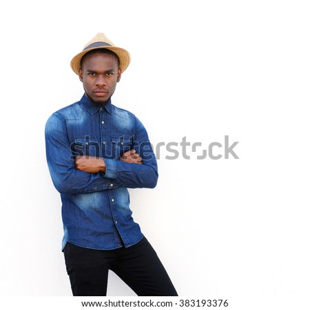 Portrait of a cool young man with hat standing against white background - stock photo