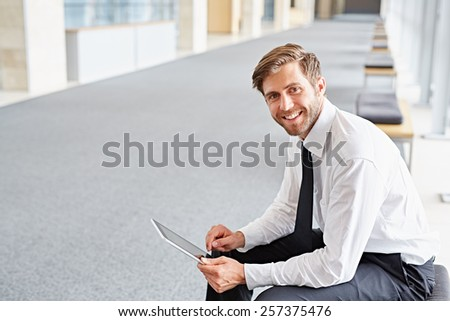 Portrait of a corporate executive smiling while using a digital tablet - stock photo