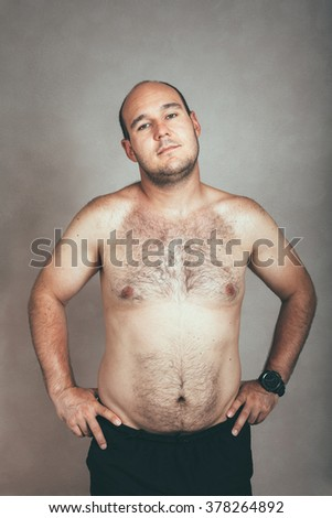Portrait of a corpulent hairy shirtless man. - stock photo