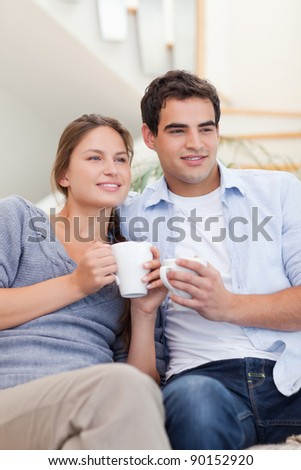 Portrait of a couple drinking coffee while watching TV in their living room - stock photo