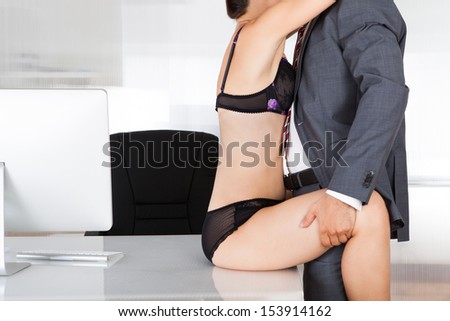 Portrait of a couple having sex in office - stock photo