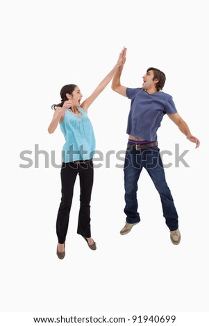 Portrait of a couple jumping together against a white background