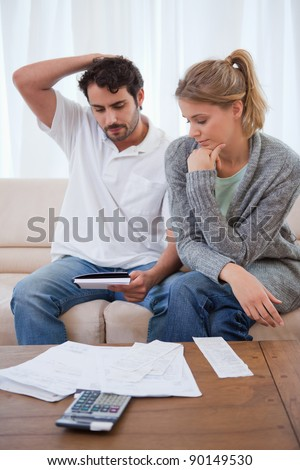 Portrait of a couple looking at their bills in their living room - stock photo