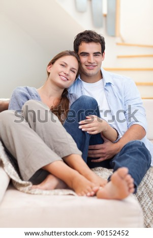 Portrait of a couple lying on a sofa while looking at the camera - stock photo