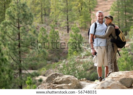 Portrait of a couple of hikers embracing - stock photo