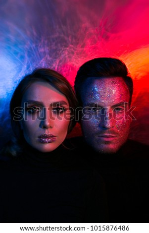 portrait of a couple of men and a woman, with sparkles on their faces. Fashion photo in color light. Art make-up. Fashion Model with Colorful Makeup