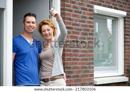 Portrait of a couple smiling and holding keys to their new house - stock photo