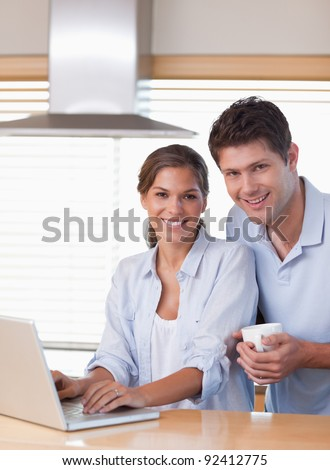 Portrait of a couple using a laptop while having coffee in their kitchen
