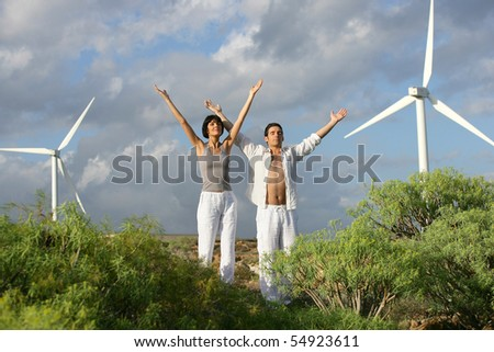 Portrait of a couple with arms up next to wind turbines