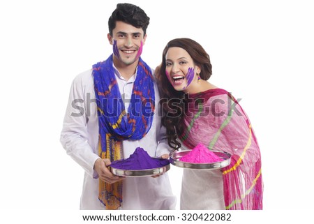 Portrait of a couple with holi colours enjoying - stock photo