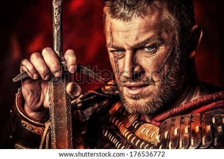 Portrait of a courageous ancient warrior in armour with sword. - stock photo