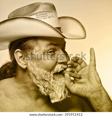 Portrait of a cowboy smoking a cigar at the time of dyeing his beard studio - stock photo