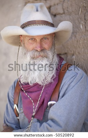 Portrait of a cowboy wearing a tall hat and sporting a long white beard. He is dressed in a heavy work shirt and kerchief. Vertical shot. - stock photo
