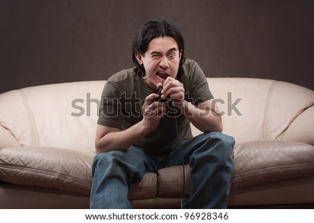 portrait of a crazy gamer on gray background - stock photo