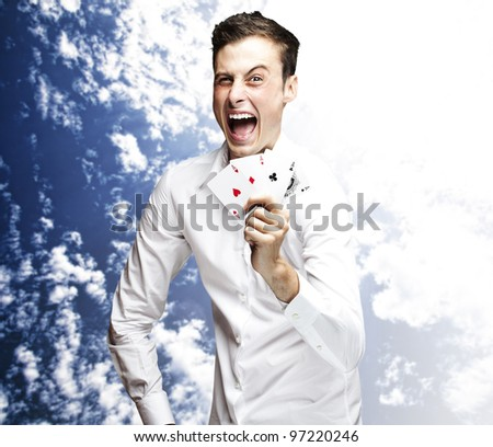 portrait of a crazy man showing poker cards against a blue sky background - stock photo