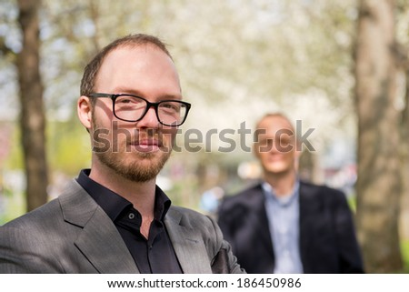 Portrait of a creative business professional, with his aide behind him in the background - stock photo
