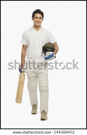 Portrait of a cricket batsman walking with a bat and a helmet - stock photo