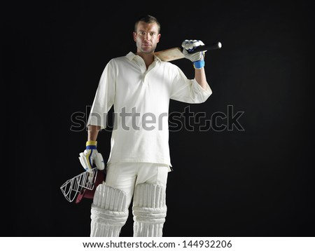 Portrait of a cricket player holding bat and helmet against black background - stock photo