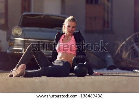 Portrait of a crossfit woman sitting on the street after her workout - stock photo