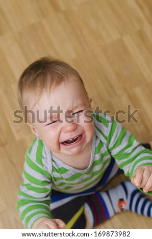 portrait of a crying baby boy sitting on the floor - stock photo