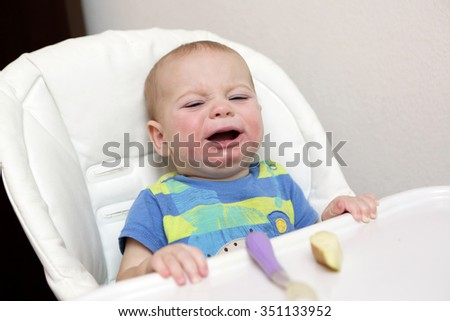 Portrait of a crying baby in highchair at home - stock photo