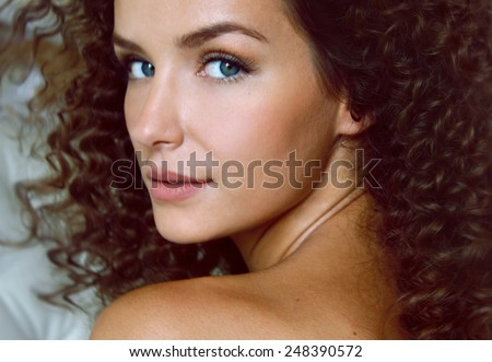 Portrait of a curly girl with blue eyes with bared shoulders sitting back - stock photo
