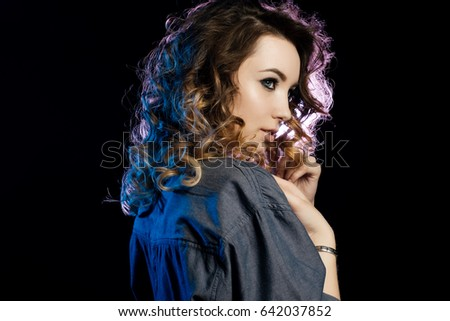 Portrait of a curly-haired girl in a blue shirt standing in half-turn on dark background. Horizontal photo