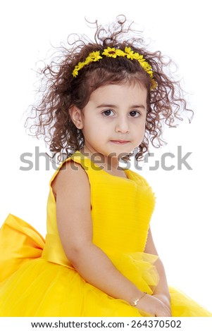 Portrait of a curly-haired girl with yellow flowers in her hair and a yellow dress - stock photo