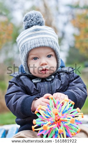 Portrait of a cute baby boy with a ball outdoors in autumn - stock photo