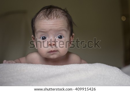 Portrait of a cute baby crawling in bed, looking at camera - stock photo
