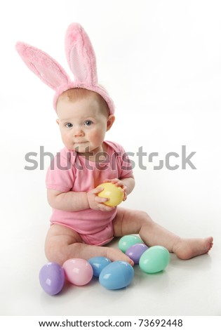 Portrait of a cute baby dressed in Easter bunny ears with a basket full of eggs - stock photo