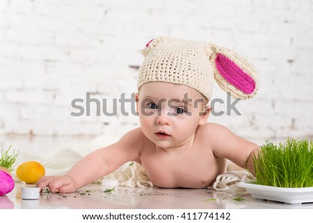 Portrait of a cute baby dressed in Easter bunny suit playing carrot and easter eggs
