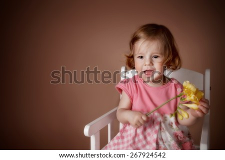 Portrait of a cute baby girl with flower - stock photo