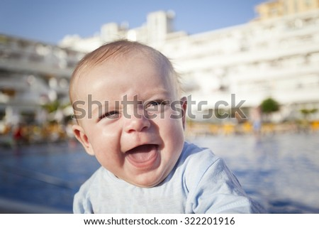 Portrait of a cute baby laughing outdoors - stock photo