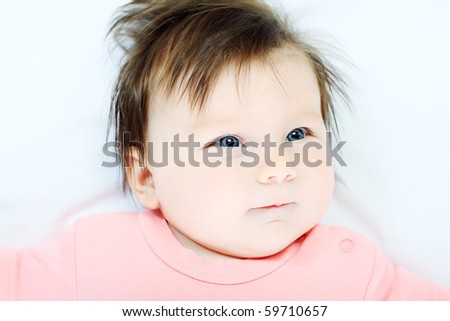 Portrait of a cute baby lying on a white towel.