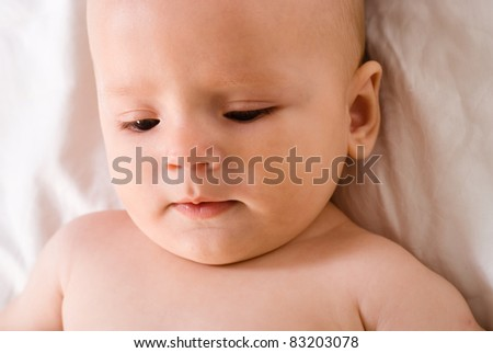 portrait of a cute baby lying on bed on a white