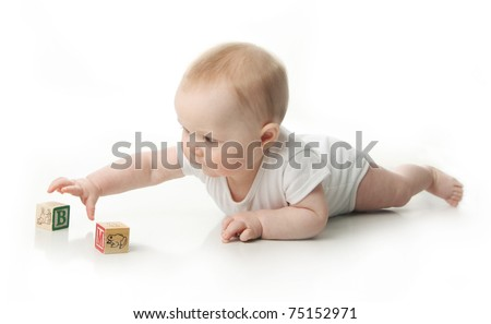 Portrait of a cute baby sitting playing with wooden blocks - stock photo