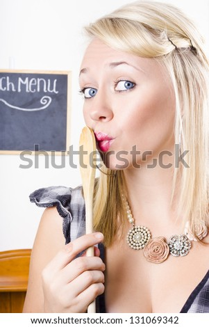 Portrait Of A Cute Blonde Female Cook With Expression Of Surprise Standing Holding Wooden Spoon To Mouth When Hiding A Secret Recipe