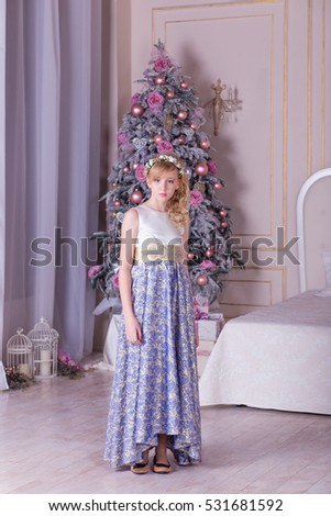Portrait of a cute blonde in a beautiful evening dress in the Christmas decoration. Pretty girl posing in a Christmas tree