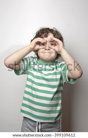 Portrait of a cute boy making binoculars with his hands. A cute child wearing a green striped t-shirt is making binoculars with his both hands in front of a white background. - stock photo