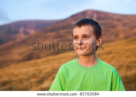 Portrait of a cute boy on Parang mountains, Romania, at sunset - stock photo