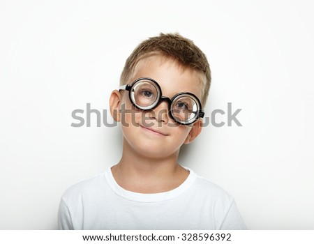 Portrait of a cute boy on the white wall background and wearing glasses