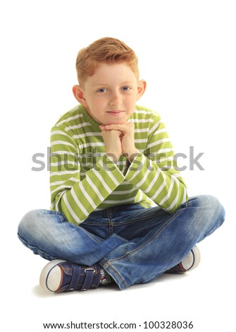 Portrait of a cute boy sitting on the floor on white background - stock photo