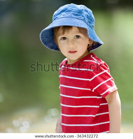 Portrait of a cute boy with summer hat on a edge of a river, playing - stock photo