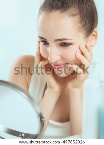 Portrait of a cute brunette woman touching her cheeks by her both hands