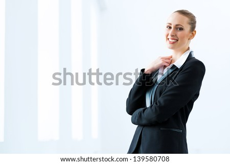 Portrait of a cute business woman stands with his arms crossed
