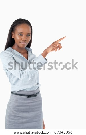 Portrait of a cute businesswoman pressing an invisible key against a white background
