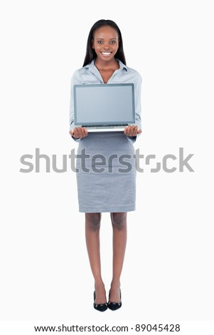 Portrait of a cute businesswoman showing a laptop against a white background