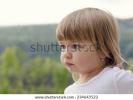 Portrait of a cute but sad looking  child girl, natural outdoor profile portrait. - stock photo