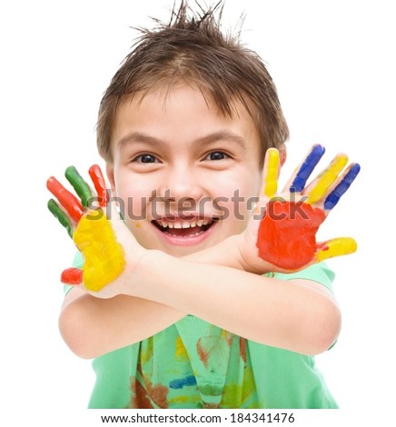 Portrait of a cute cheerful boy showing her hands painted in bright colors, isolated over white - stock photo